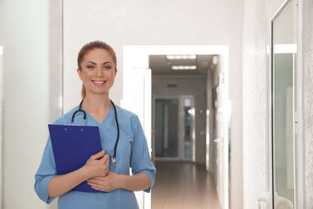 Portrait of nurse with clipboard in hospital hallway. Medical assisting