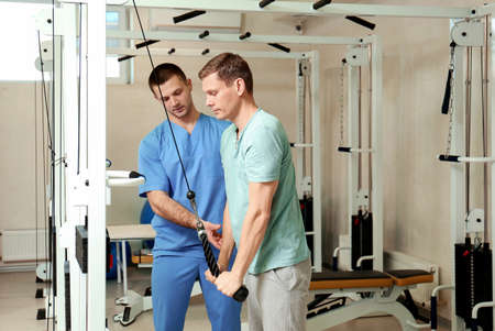 Patient exercising under physiotherapist supervision in rehabilitation center