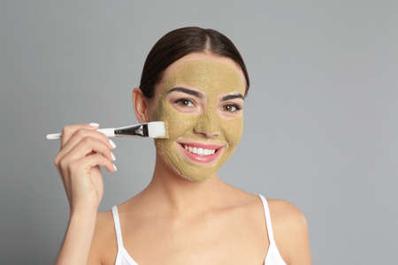 Young woman applying clay mask on her face against grey background