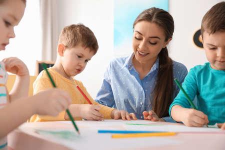 Petits enfants avec un enseignant de maternelle dessinant à table à l'intérieur. Apprendre et jouer Banque d'images