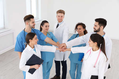 Team of medical workers holding hands together in hospital. Unity concept