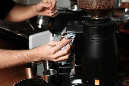 Barista cleaning coffee grinding machine with rag in cafe, closeup