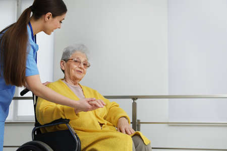Nurse assisting senior woman in wheelchair at hospital