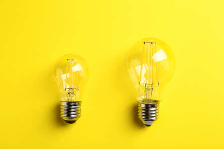 Vintage filament lamp bulbs on yellow background, top view
