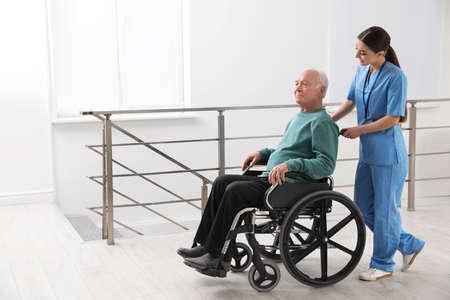 Nurse assisting senior man in wheelchair at hospital