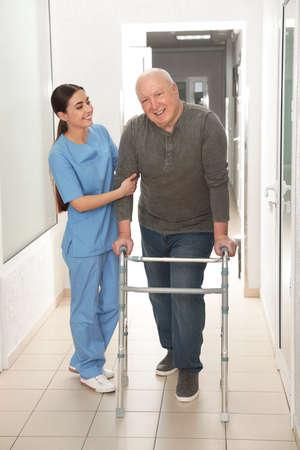 Nurse assisting senior patient with walker in hospital hallway