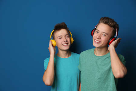Teenage twin brothers with headphones on color background