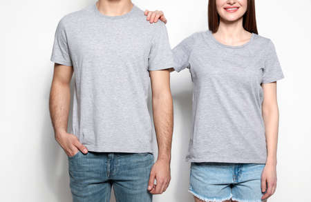 Young people in t-shirts on light background, closeup. Mock up for design Фото со стока