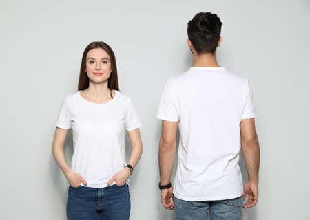 Junge Leute in T-Shirts auf hellem Hintergrund. Mock-up für Design