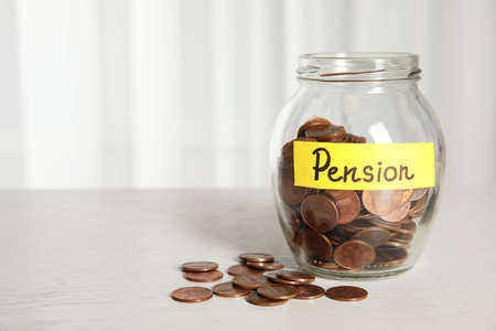 Glass jar with label PENSION and coins on white table. Space for text