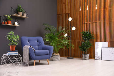 Room interior with armchair and indoor plants. Trendy home decor Stock Photo