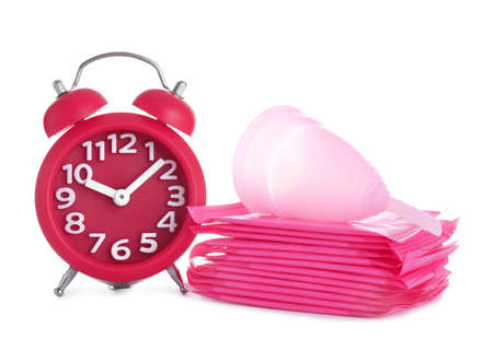 Clock, menstrual pads and cup on white background. Gynecology concept