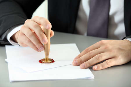 Male notary sealing document at table, closeup Archivio Fotografico