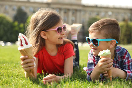 Cute children with delicious ice creams on grass outdoors