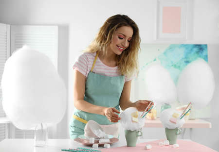 Young woman with cup of cotton candy dessert at table in room