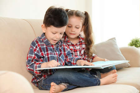 Cute children reading book on sofa in living room