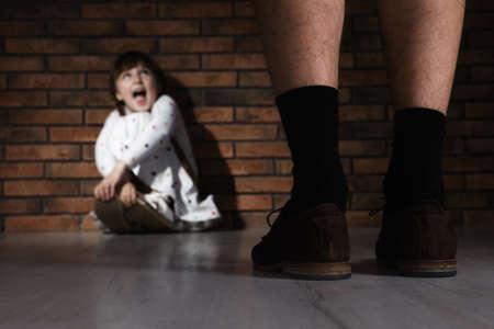 Hombre adulto sin pantalones de pie delante de una niña asustada en el interior. Niño en peligro Foto de archivo