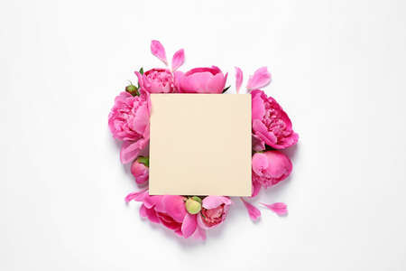 Fresh peonies and empty card on white background, top view with space for text