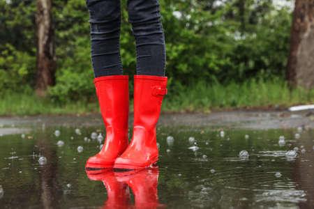 Vrouw in rode rubberen laarzen op regenachtige dag buitenshuis, close-up