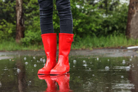 Woman in red rubber boots on rainy day outdoors, closeup