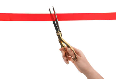 Woman cutting red ribbon with scissors on white background. Traditional ceremony