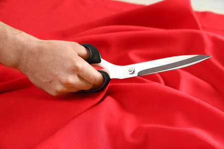 Professional tailor cutting red fabric with scissors in workshop, closeup