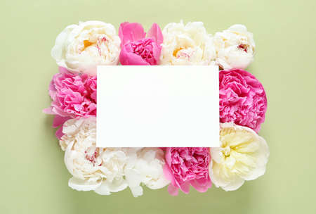 Fresh peonies and empty card on color background, flat lay with space for text