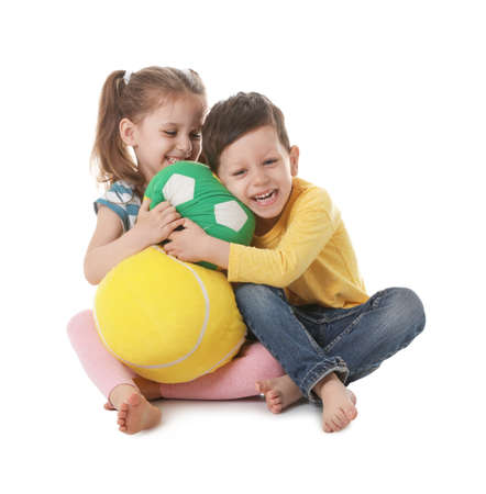 Cute little boy and girl with soft balls on white background Stockfoto