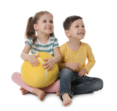 Cute little boy and girl with soft ball on white background Stockfoto