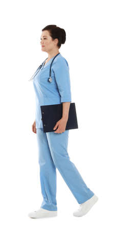 Full length portrait of female doctor in scrubs with clipboard isolated on white. Medical staff