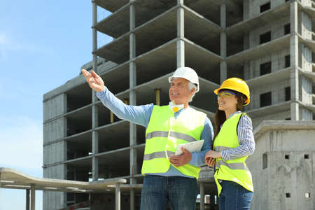 Professional engineer and foreman with tablet in safety equipment at construction site