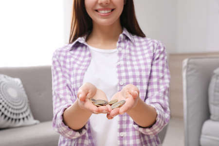 Happy woman holding coins in hands at home Stock fotó