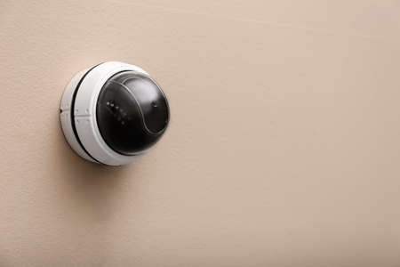 Modern CCTV security camera on beige wall. Space for text