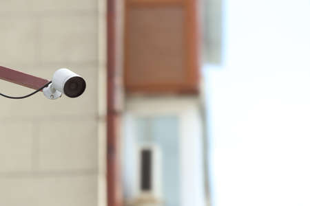 Modern CCTV security camera on building wall outdoors. Space for text