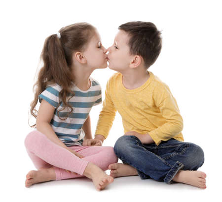 Cute little boy and girl kissing on white background