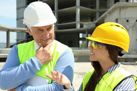 Professional engineers in safety equipment at construction site Banque d'images