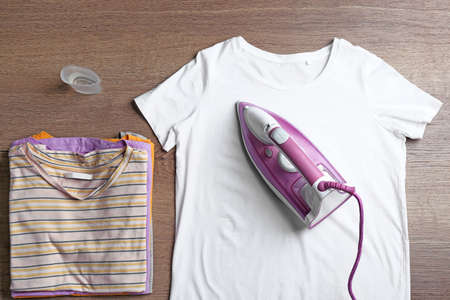 Flat lay composition with clothes and modern iron on wooden table