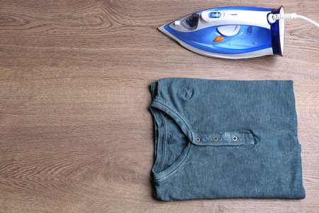 Flat lay composition with folded clothes and iron on wooden table. Space for text Standard-Bild