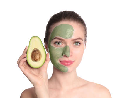 Young woman with clay mask on her face holding avocado against white background. Skin care