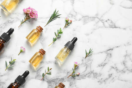 Flat lay composition with bottles of natural tea tree oil and space for text on white marble background 版權商用圖片