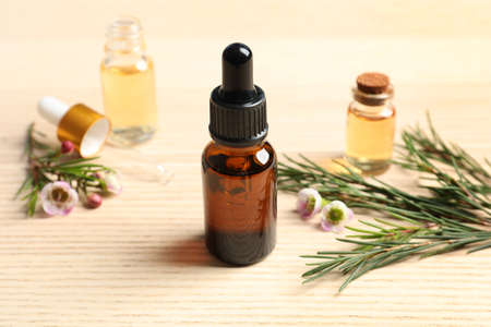 Composición con botella de aceite de árbol de té natural sobre mesa de madera