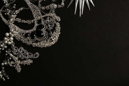 Different elegant jewelry on black background, top view. Space for text