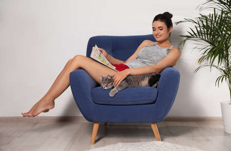 Young woman with cat and magazine on armchair at home. Cute pet
