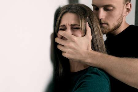Hombre abusando de mujer joven cerca de la pared de luz, espacio para texto. Detener el asalto