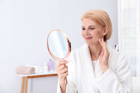Mature woman with mirror applying face cream at home Imagens