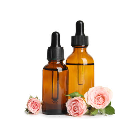 Bottles of rose essential oil and flowers isolated on white background