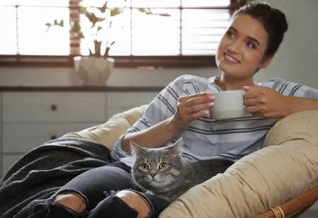 Jonge vrouw met schattige kat op fauteuil thuis. Huisdier en eigenaar