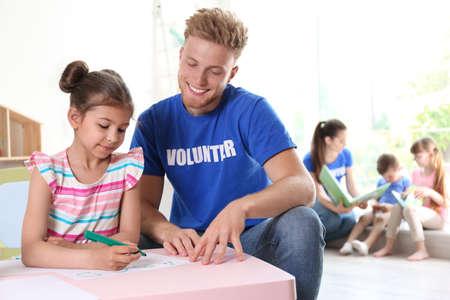 Petite fille apprenant l'alphabet avec un volontaire à table à l'intérieur