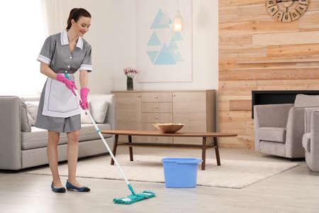 Kamermeisje wasvloer met dweil in hotelkamer. Ruimte voor tekst Stockfoto