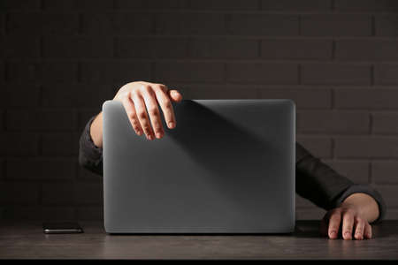 Woman lying on laptop at table in dark room. Loneliness concept